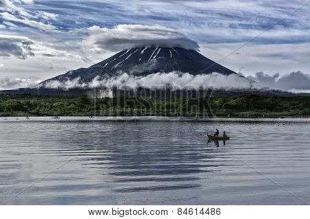 Two fisher men fish in front of Mt Fuji