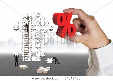 Hand Holding Percentage Sign With Businessmen Building Arrow Jigsaw Puzzle