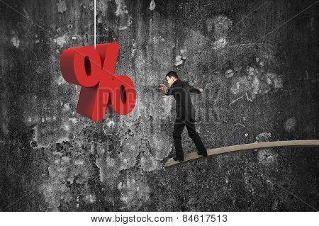 Businessman Balancing On Wooden Board With Red Percentage Sign