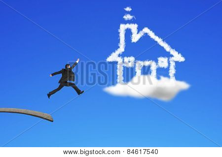 Businessman Jumping From Wooden Board To House Shape Cloud
