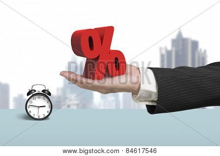 Hand Showing Red Percentage Sign With Alarm Clock And Cityscape
