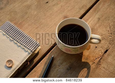 A cup of coffee and diary on wood table in early morning