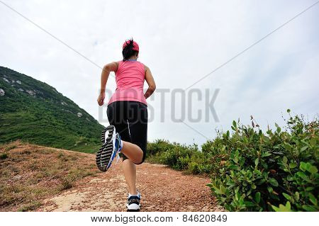 young woman runner running on seaside mountain trail