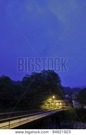 An abandon house sits under a street light at dusk