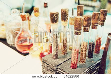 Spices and various bitters in old-styled bar, toned image