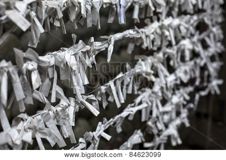 Paper prayers tied to a fence