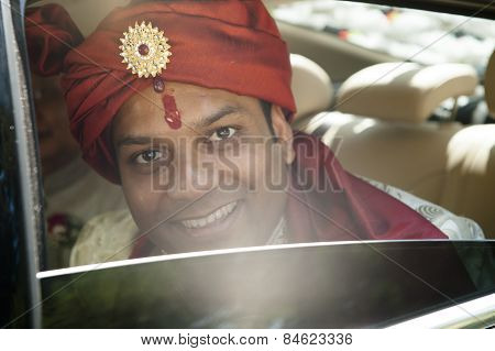 Handsome young Hindu Groom smiling out of car window in traditional attire