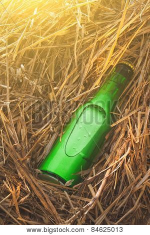 Beer bottle in the stack of hay. Without label, green glass