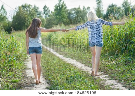 Friends Walking On Country Road Together