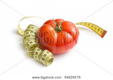red tomato and measuring tape on white background