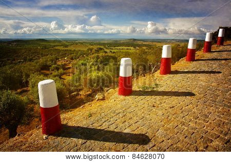 A row of red and white roadside pillars in a rural landscape