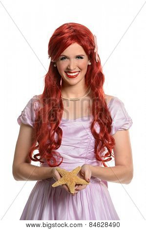 Portrait of beautiful yong woman dresses in princess costume holding starfish isolated over white background