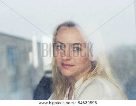 Beautiful blonde woman looking through the window on a rainy day