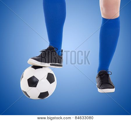 Legs Of Soccer Player And Ball Close-up Over Blue