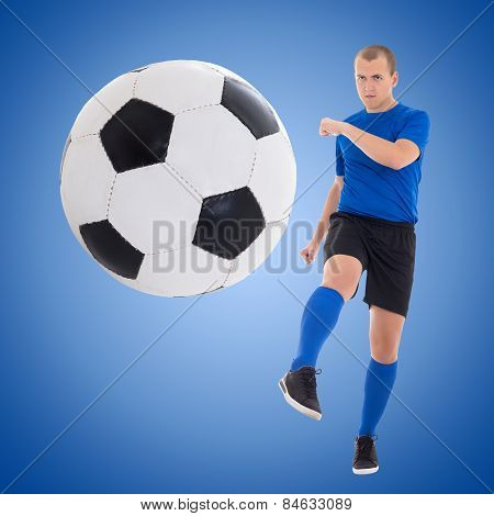Young Soccer Player Kicking Ball Over Blue