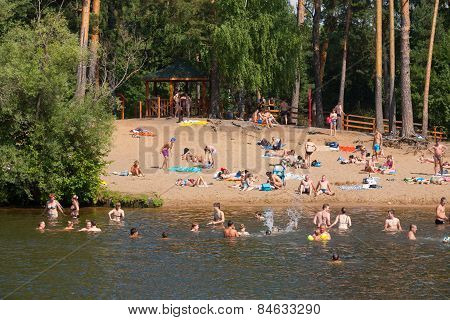 People Swimming And Sunbathing In Moskva River Beach At Serebryany Bor