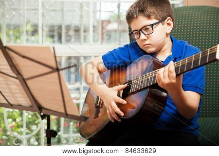 Boy Reading A Guitar Sheet Music