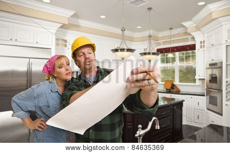Male Contractor in Hard Hat Discussing Plans with Woman in Custom Kitchen Interior.