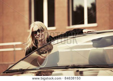 Happy young fashion woman at the convertible car