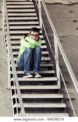 Teen boy in depression sitting on the steps