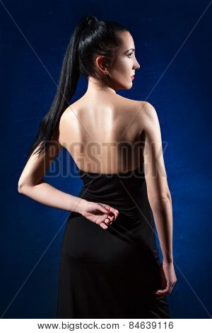 Girl In Black Dress On A Blue Background Posing Back