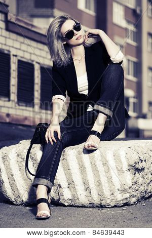 Beautiful fashion woman in sunglasses sitting on the city sidewalk