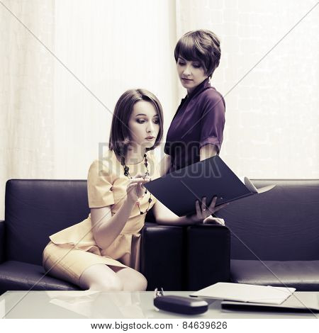 Two young fashion business women with a folder in office