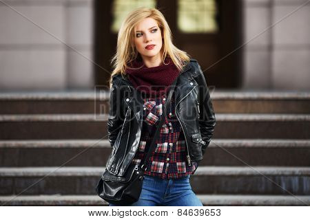 Young fashion blond woman in leather jacket on the steps
