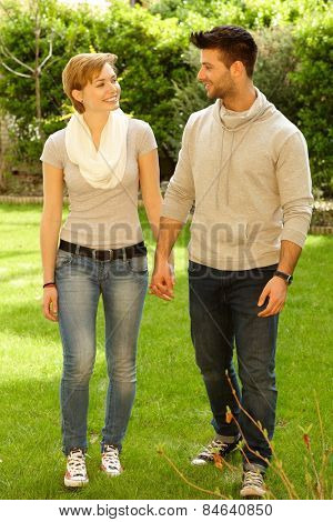 Happy young couple walking outdoors hand in hand, smiling. Full size.