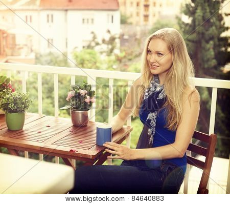 Young nordic woman sitting on balcony, drinking tea, looking away.