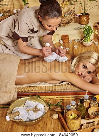 Blond woman getting herbal ball massage in spa. Masseuse standing on tracks