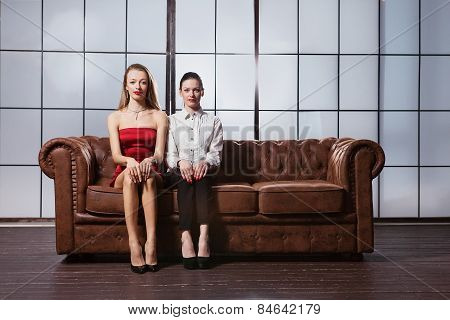 Beautiful Girls Are Sitting On The Sofa.