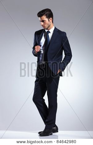 Side view picture of a elegant business man holding one hand in his pocket while pulling his jacket.