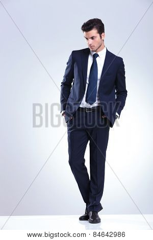 Full length picture of a young elegant business man looking down while holding both hands in his pockets.
