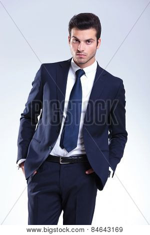 Attractive business man posing on grey studio background with his hands in pockets, looking at the camera.