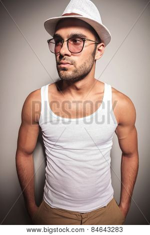 Handsome casual fashion man posing against a white wall, looking away with his hands in pockets.