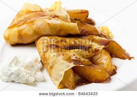 English-style pancakes filled with caramelised pears, topped with light caramel sauce and served with yoghurt.