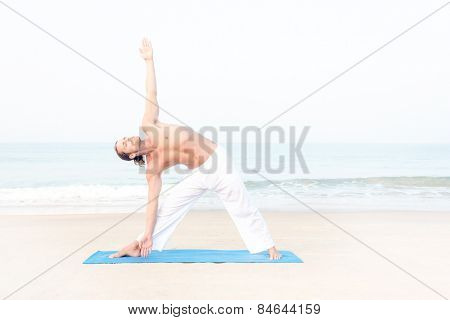 Fit man performing yoga at the beach