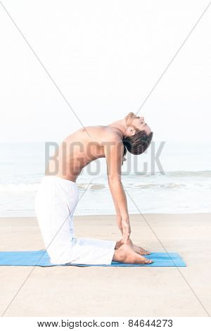 Fit man performing yoga asana on the beach