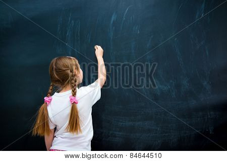 little girl in a white T-shirt with pigtails writing with chalk on chalkboard