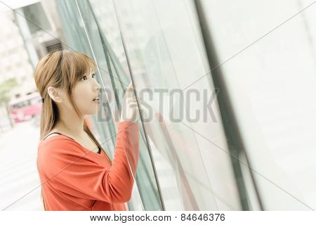 Shopping woman looking the window glass at store in Xinyi district, the business and commercial center in Taipei, Taiwan, Asia.