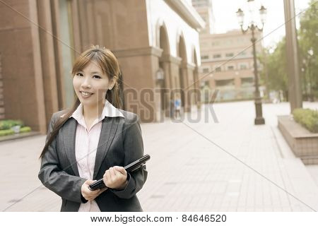 Attractive young business woman hold a laptop and look at you, shot at Xinyi business district, Taipei, Taiwan.