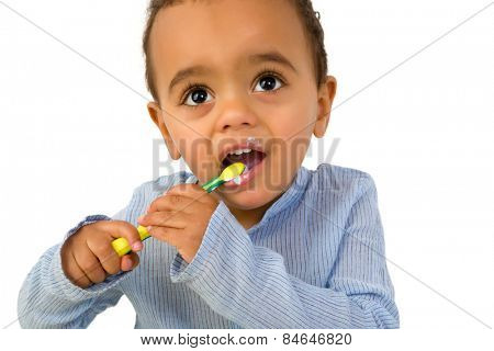 Smiling 18th month old African toddler boy brushing his teeth