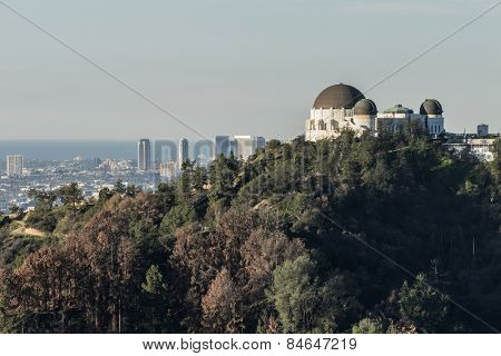 LOS ANGELES, CALIFORNIA, USA - January 14, 2015:  The famous Griffith Park Observatory with Century City towers and the pacific ocean in background.