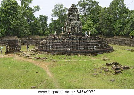 Tourists explore the Neak Pean temple in Angkor, Cambodia.