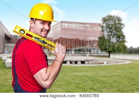 smiling manual worker with spirit level