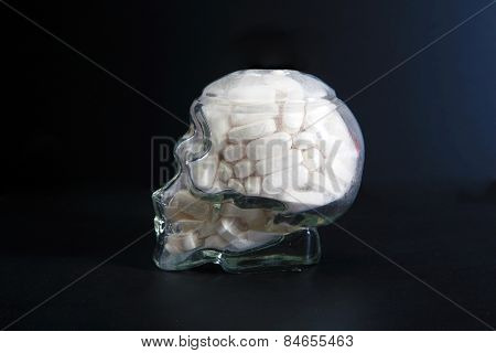 a Glass or Crystal Skull filled with white pills. Represents Pharmacology and Brain Chemistry, Drug Abuse, Schizophrenia, Drug Abuse, Prescription Drug Dependence, Chemistry, and other concepts.