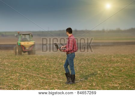 Peasant With Laptop On Farmland