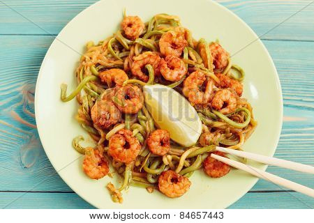 shrimps and zucchini noodles in green plate with chopsticks, toned