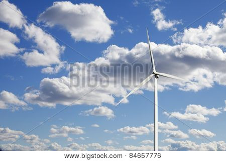 wind power and clear blue sky with puffy white clouds